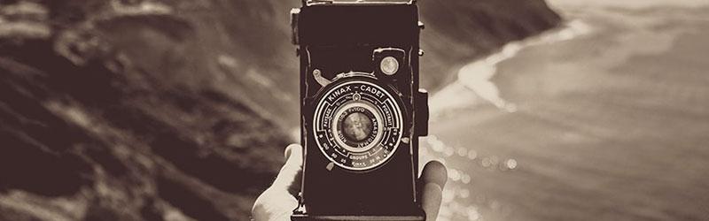 Mão segurando uma câmera antiga com o efeito preto e branco do preset