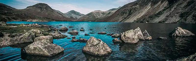 Paisagem com um lago, pedras e montanhas ao fundo