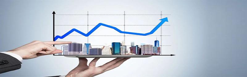 Uma mão segurando uma bandeja com prédios e um gráfico crescente.