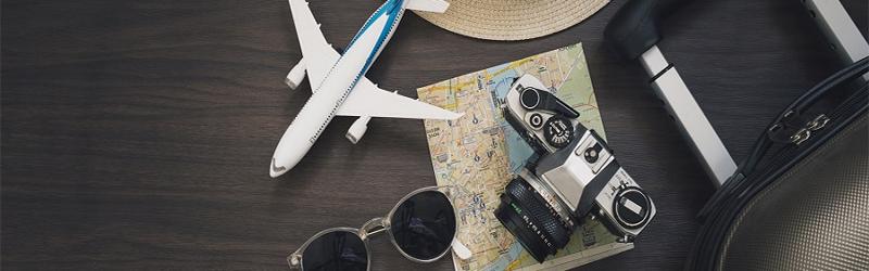 Uma foto de um óculos, uma câmera em cima de um mapa dobrado, uma mala e um avião em miniatura, todos em cima de uma mesa.