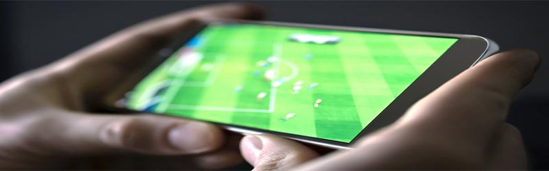 Foto de duas mão segurando um celular na horizontal enquanto passa um jogo de futebol.