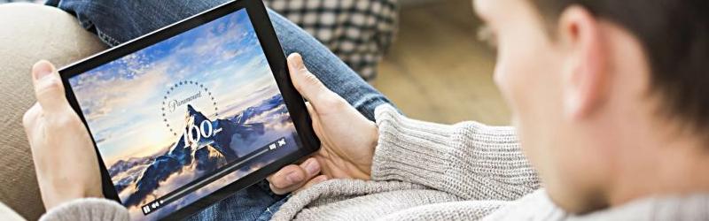 Foto de um homem sentado assistindo filme em um tablet.