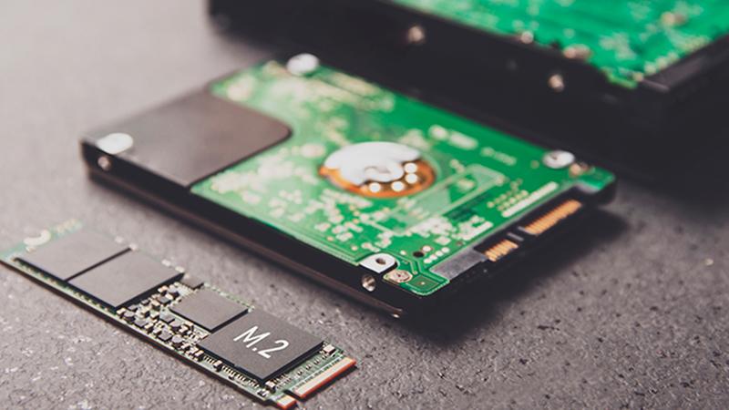 Um HD e dois SSDs com as placas de chip expostas