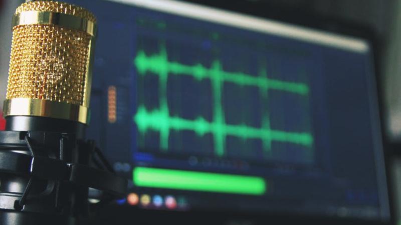 Imagem de um microfone focado e ao fundo uma tela de notebook com ondas de áudio.