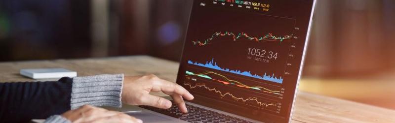 Foto de uma pessoa usando um notebook com gráficos subindo e descendo na tela.