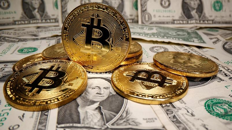 Algumas moedas de Bitcoin dourada em cima de notas de dolares