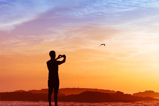 Foto da silhueta de um homem tirando foto de um pássaro voando com o por do sol ao fundo