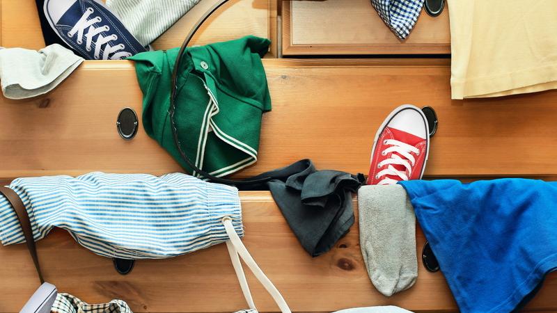 Foto de um armário com roupas e sapatos saindo das gavetas