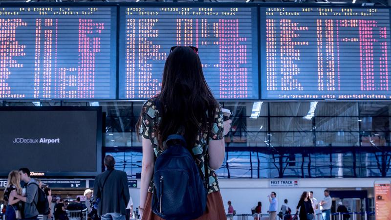 Foto de uma mulher de costas olhando para um painel de voos de um aeroporto.