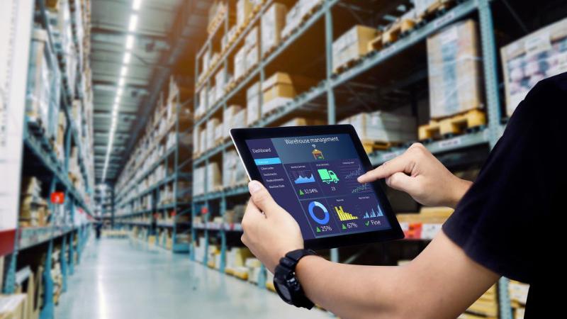 Foto de um homem em um deposito segurando um tablet com gráficos na tela