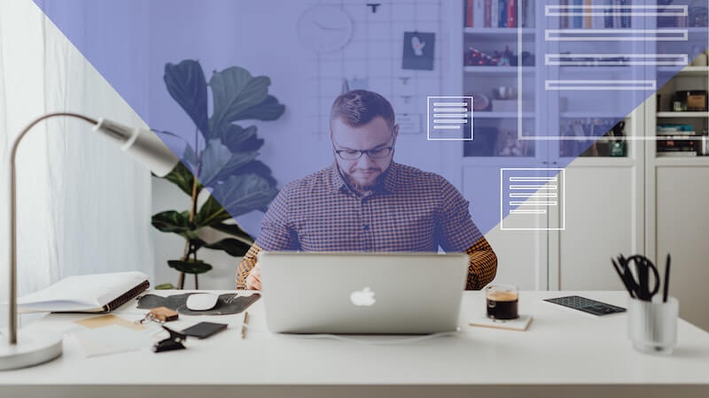 The image shows a man in his office, he is in front of a computer where pages icons a going out of it