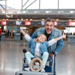 What You Need To Know About Fit To Fly Certificates: Mature man pushing daughter on trolley through airport