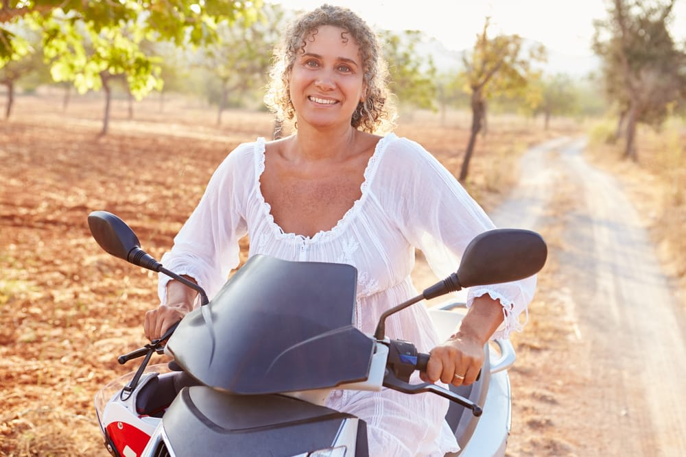 Travel Vaccinations Guide: Middle aged woman riding motor cycle on holiday