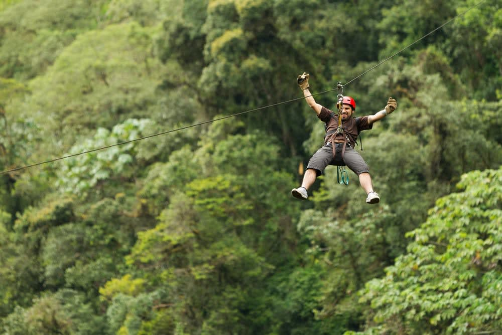 Why a bucket list is so important and how to plan one: Middle aged man on zip line adventure in Ecuadorian Rainforest