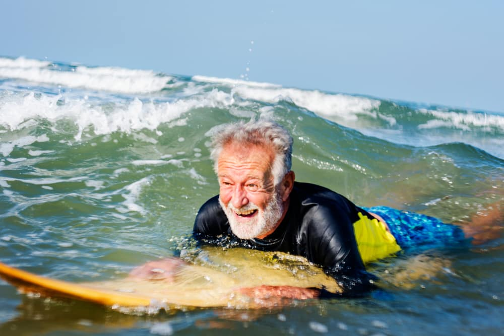 Travelling with a mental health condition: Old man surfing in the sun