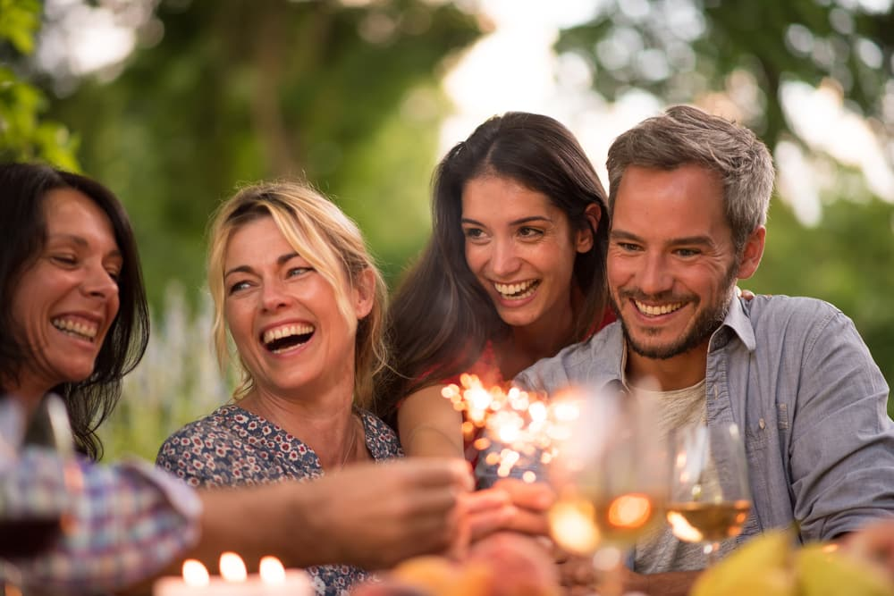 Travelling with a mental health condition: Group of friends laughing at party