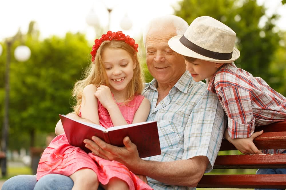15 books to read on your holiday in 2019: Grandfather reading book to children on bench