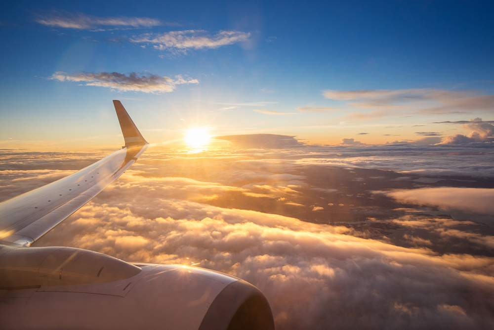 A Guide to Insurance When Airlines or Travel Companies Go Bust: View of couds and sun from plane window