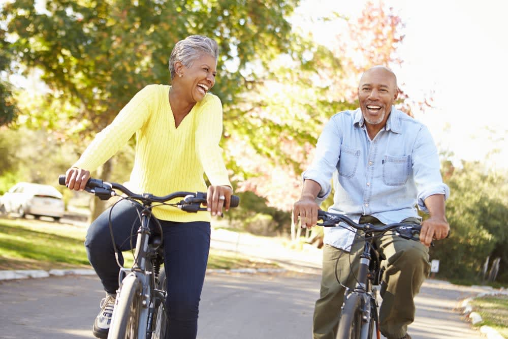 How to be a holiday eco-hero | Environmentally friendly trips: Middle aged couple riding bikes on the road