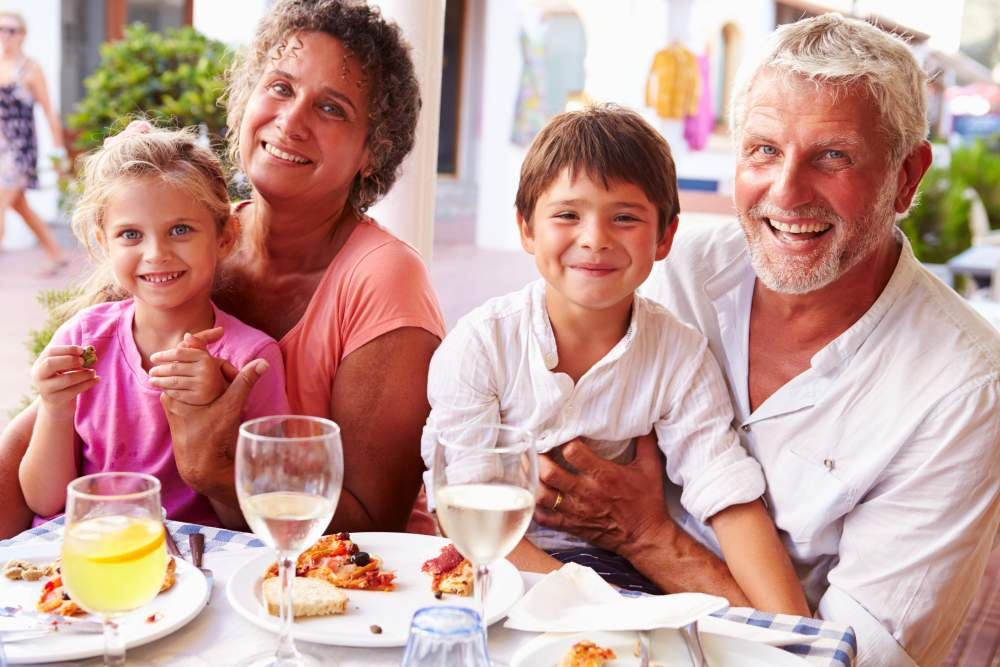 Understanding, Treating and Travelling with Eczema: Happy grandparents on holiday with kids eating dinner