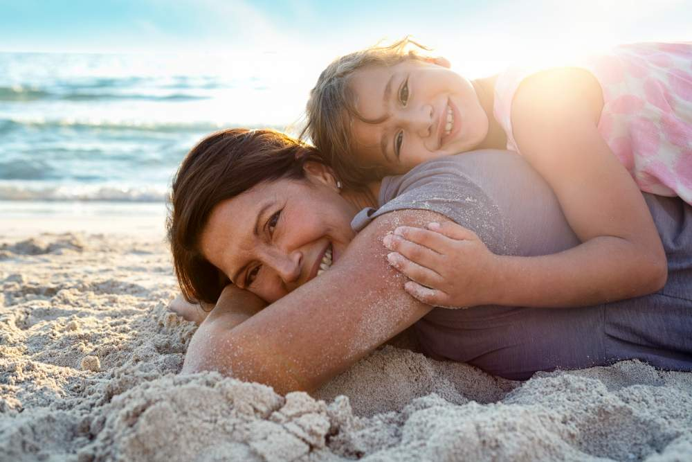 Understanding, Treating and Travelling with Eczema: Grandmother and daughter laying on the beach