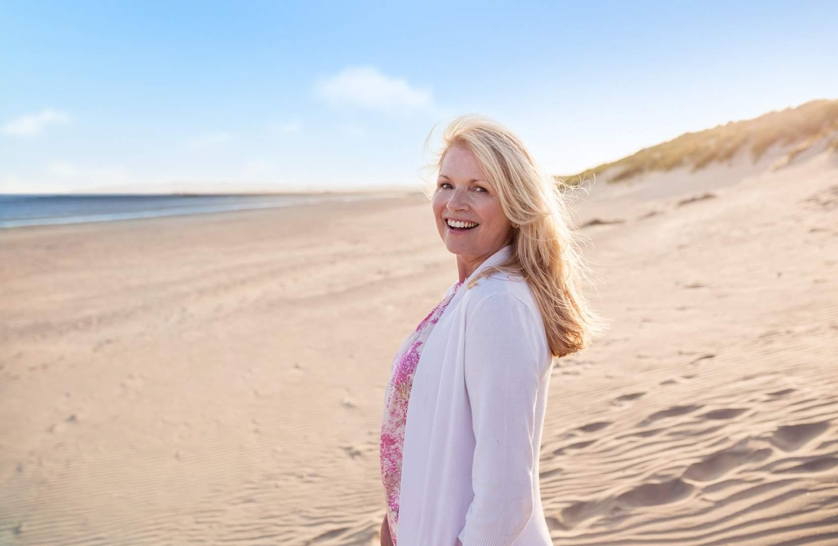 Mature woman strolling on beach as Money Saving Expert Martin Lewis Makes 2020 Travel Insurance Plea