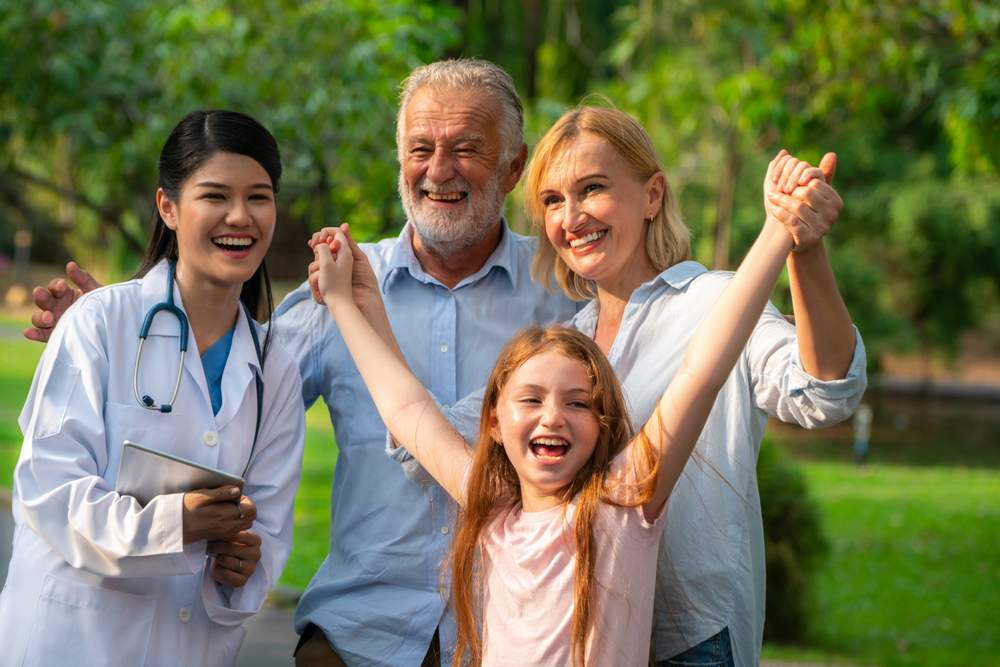 Living with a Stroke: grandfather and children laughing with female doctor
