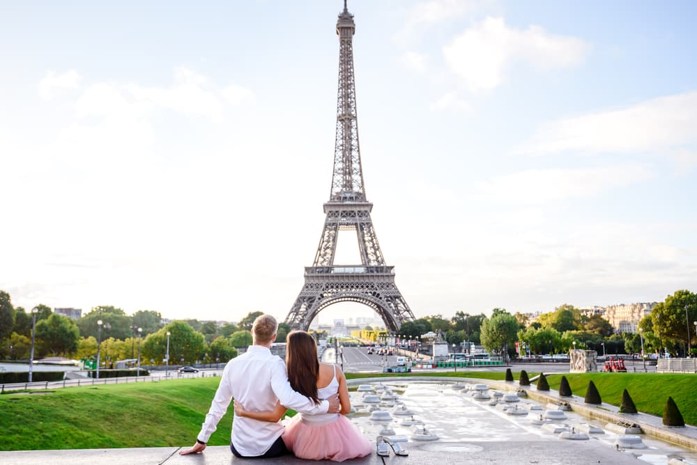Do I Need Travel Insurance? Is It Worth It? Couple sitting at Eiffel tower, in Paris