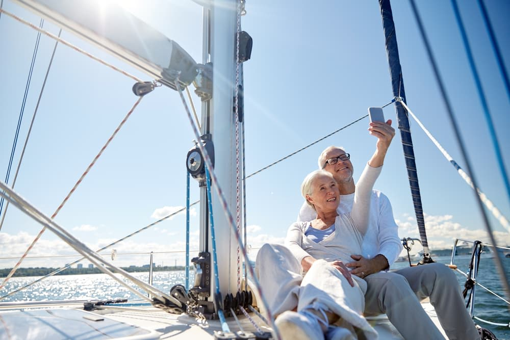 Do I Need Travel Insurance? Is It Worth It? Old couple on a cruise taking a selfie