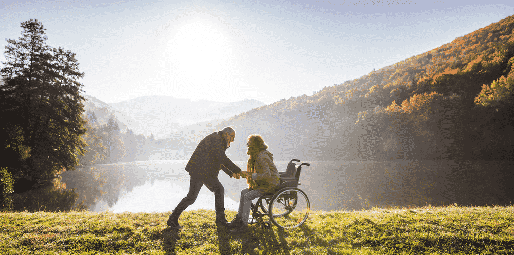 10 tips for Travelling with Someone who needs Full Time Care: Couple with disabilities enjoying holiday in the sun