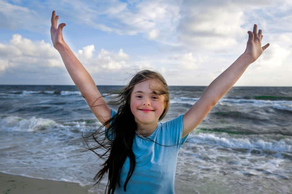 10 tips for Travelling with Someone who needs Full Time Care: Young girl with down syndrome enjoying the beach