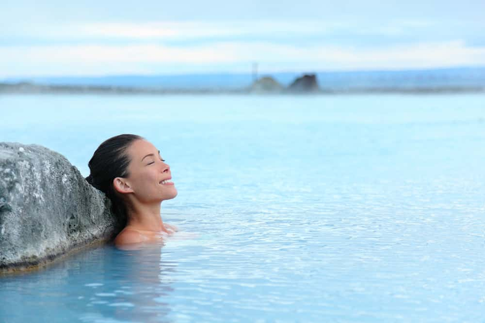 Top 10 safest countries to visit in the world 2018: young woman bathing in hot springs in Iceland