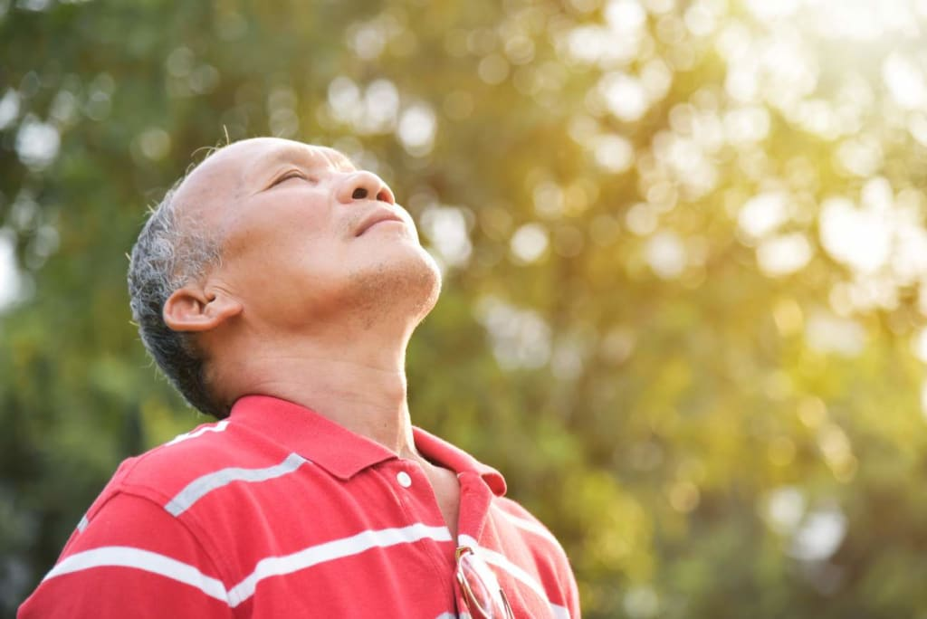 Senior man breathing in outside air