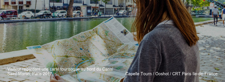 Visiteur regardant une carte touristique au bord du Canal Saint-Martin%252C Paris 2017. Capelle Tourn %252F Ooshot %252F CRT Paris Ile-de-France