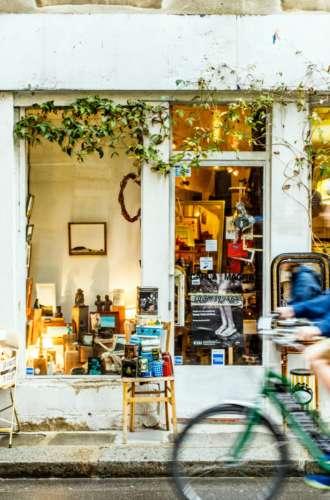 Visiteur à vélo devant une boutique du Village Saint-Paul%252C Paris 2017. Capelle Tourn %252F Ooshot %252F CRT Paris Ile-de-France