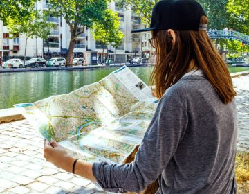Visiteur regardant une carte touristique au bord du Canal Saint-Martin, Paris 2017. Capelle Tourn / Ooshot / CRT Paris Ile-de-France