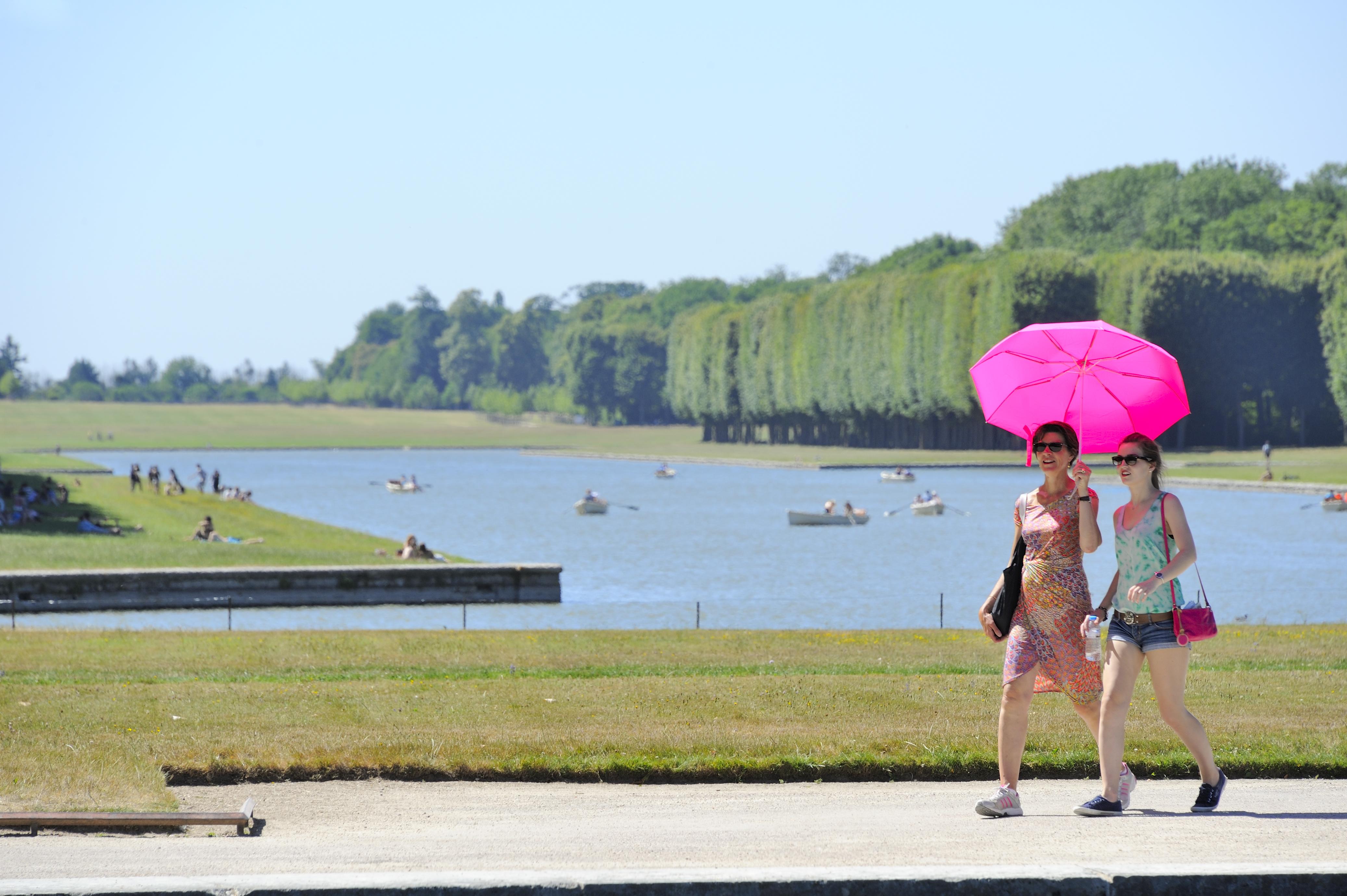 Domaine de Versailles%252C les Jardins et le Grand Canal%252C visiteurs avec parapluie rose. Jarry-Tripelon %252F CRT Paris Ile-de-France
