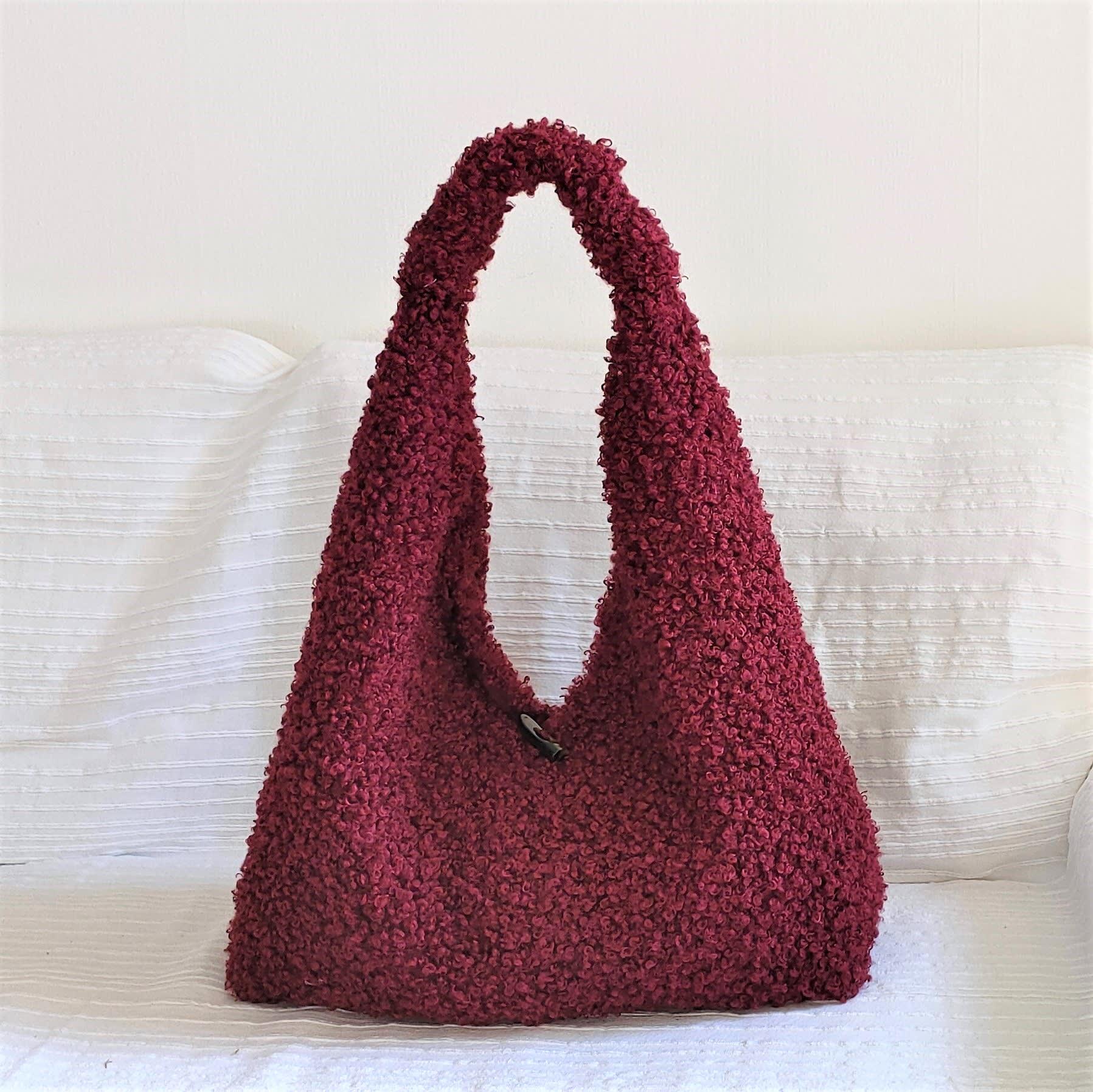 Sac besace en fausse fourrure astrakan bordeaux. Grand sac souple porté épaule couleur bordeaux.