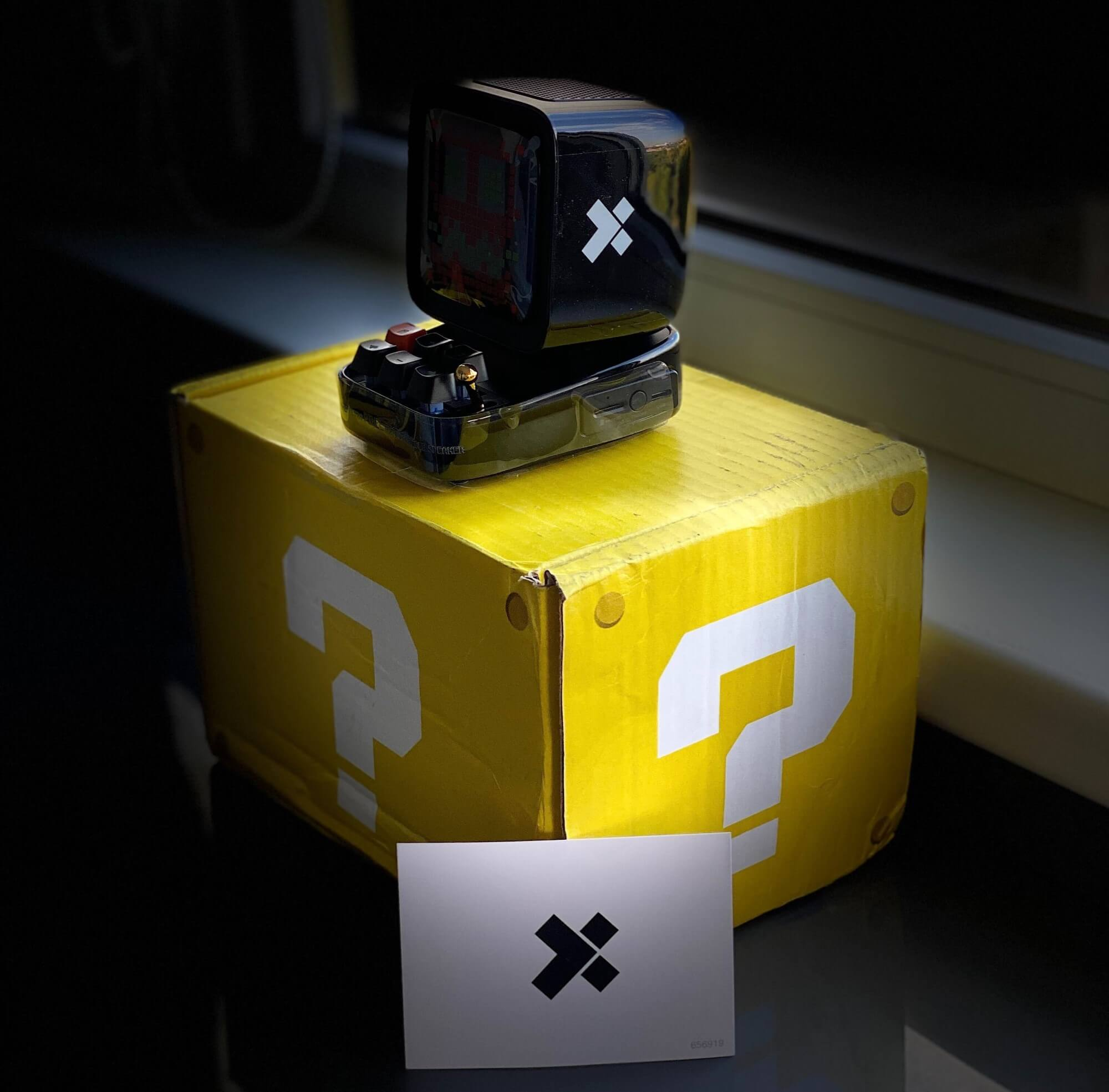 a box with a question mark, an X-Team envelope, and a Gameboy-ish device
