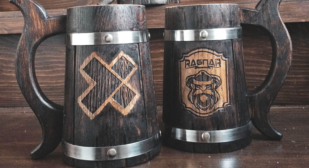 two wooden mugs with the House Ragnar and X-Team logos printed on their sides