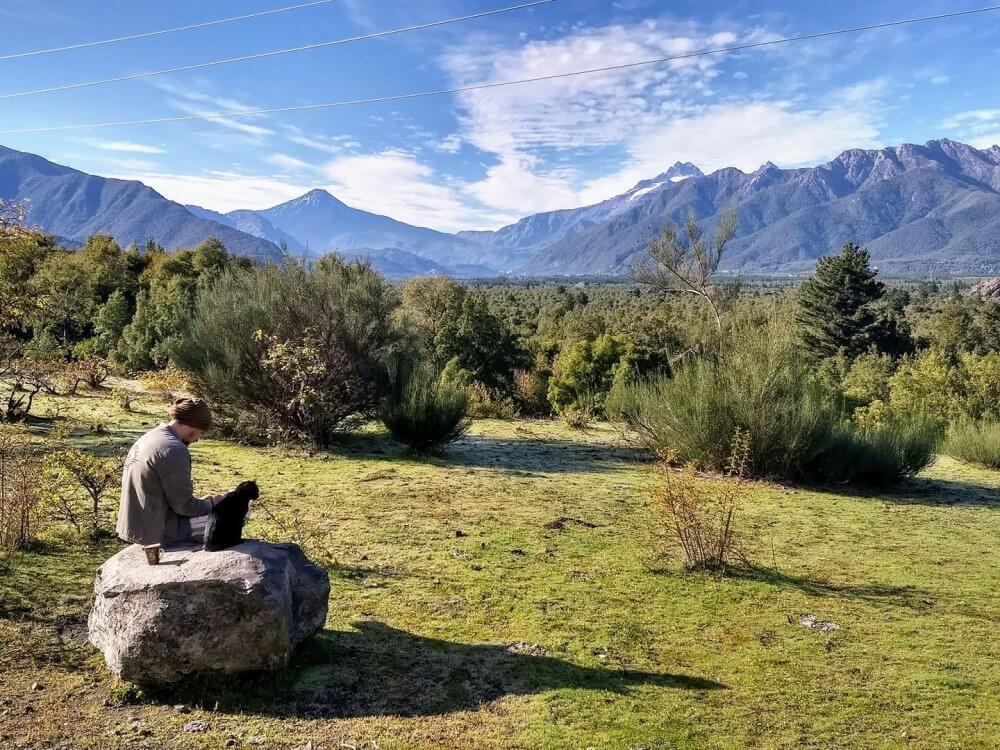 A man sitting on a rock near a mountain range