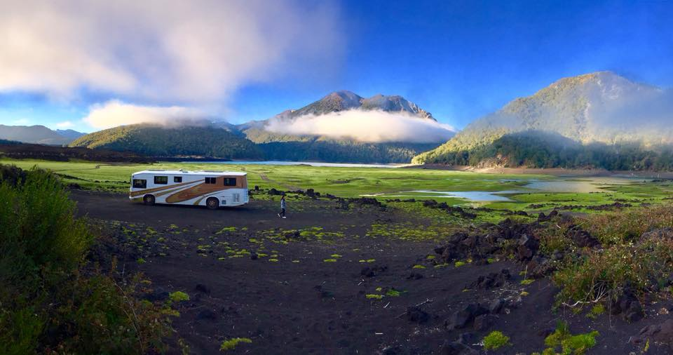 A parked RV in front of a mountain range