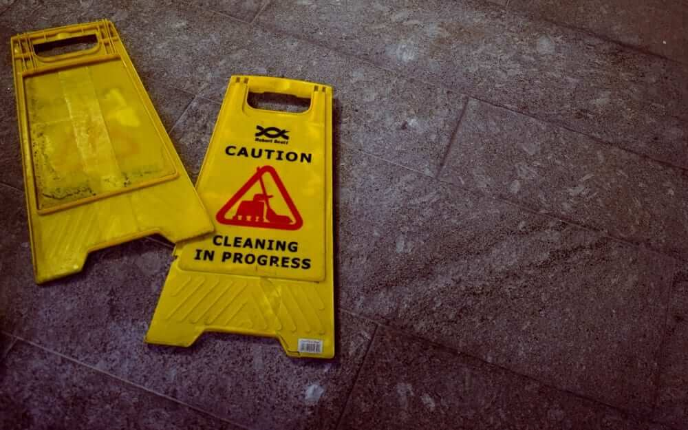 Two warning plaques that read 'cleaning in progress'