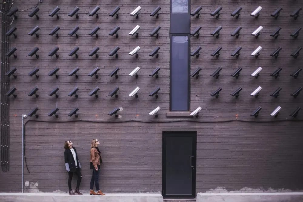 Two people looking up at dozens of cameras