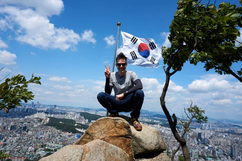 Brian sitting on a rock high up with the South Korean flag behind him