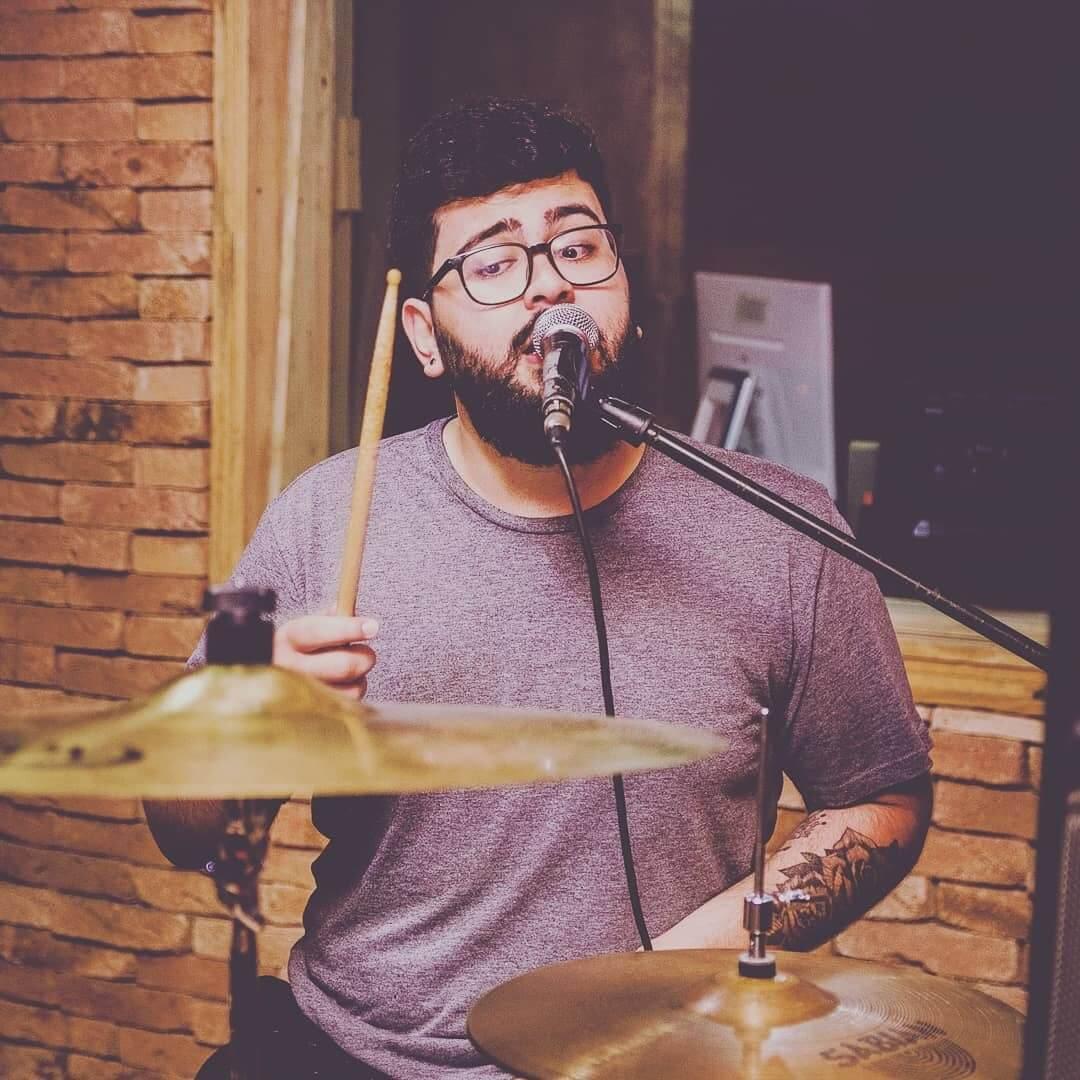 Davi playing the drums while singing