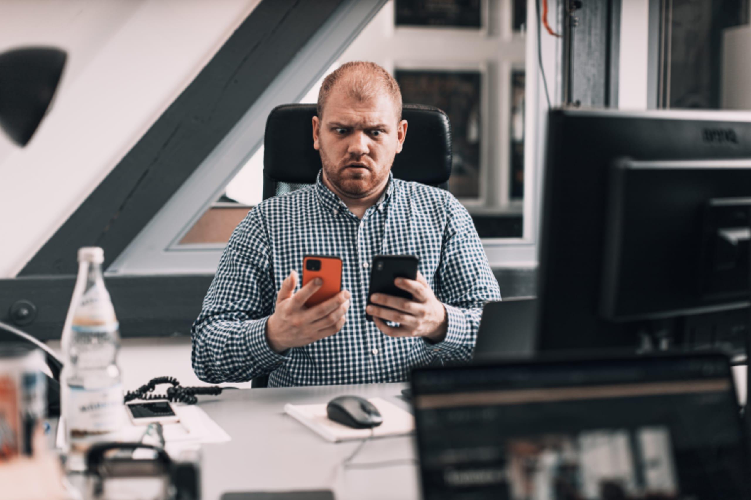 Person mit mehreren Handys in der Hand