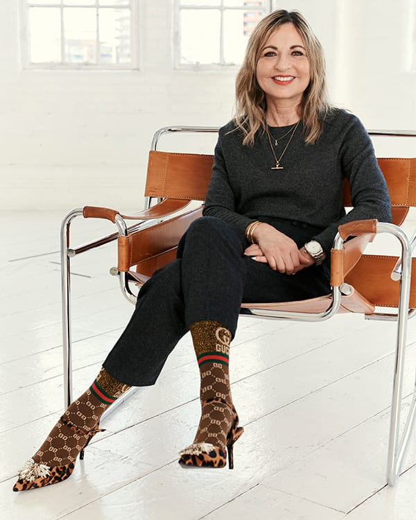 Woman sitting on a chair wearing Dune London shoes