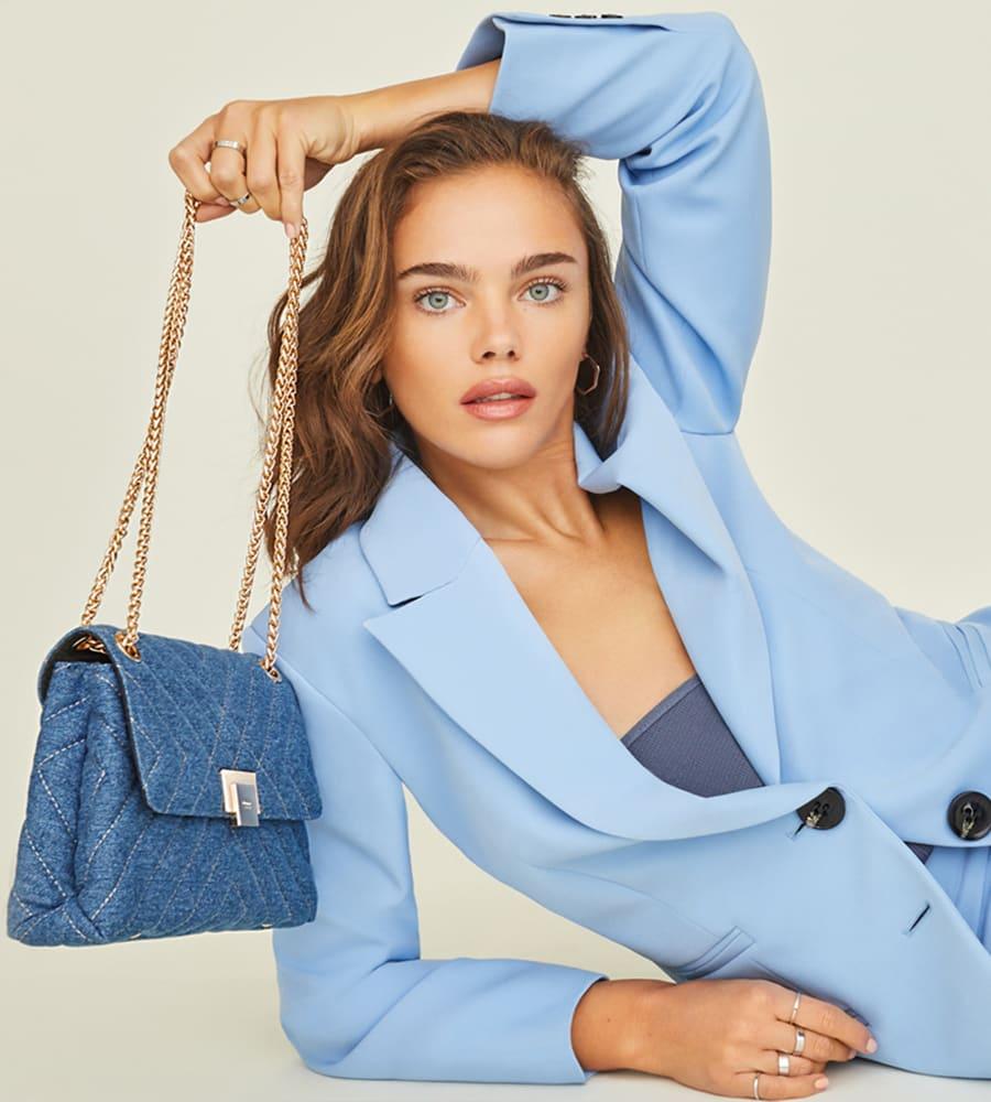 Model holding the Dorchester quilted bag in denim