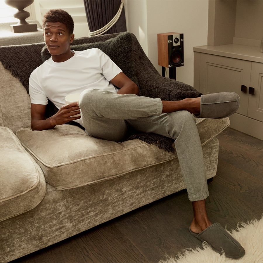 Man in White T-shirt and Grey Tracksuit bottoms with grey slippers